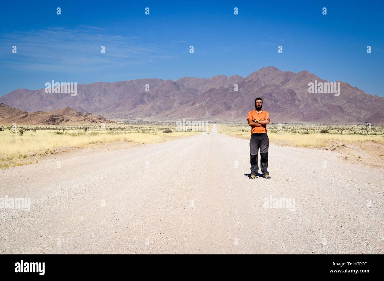Uomo in piedi sul C19 strada nel deserto del Namib, Namibia Immagini Stock