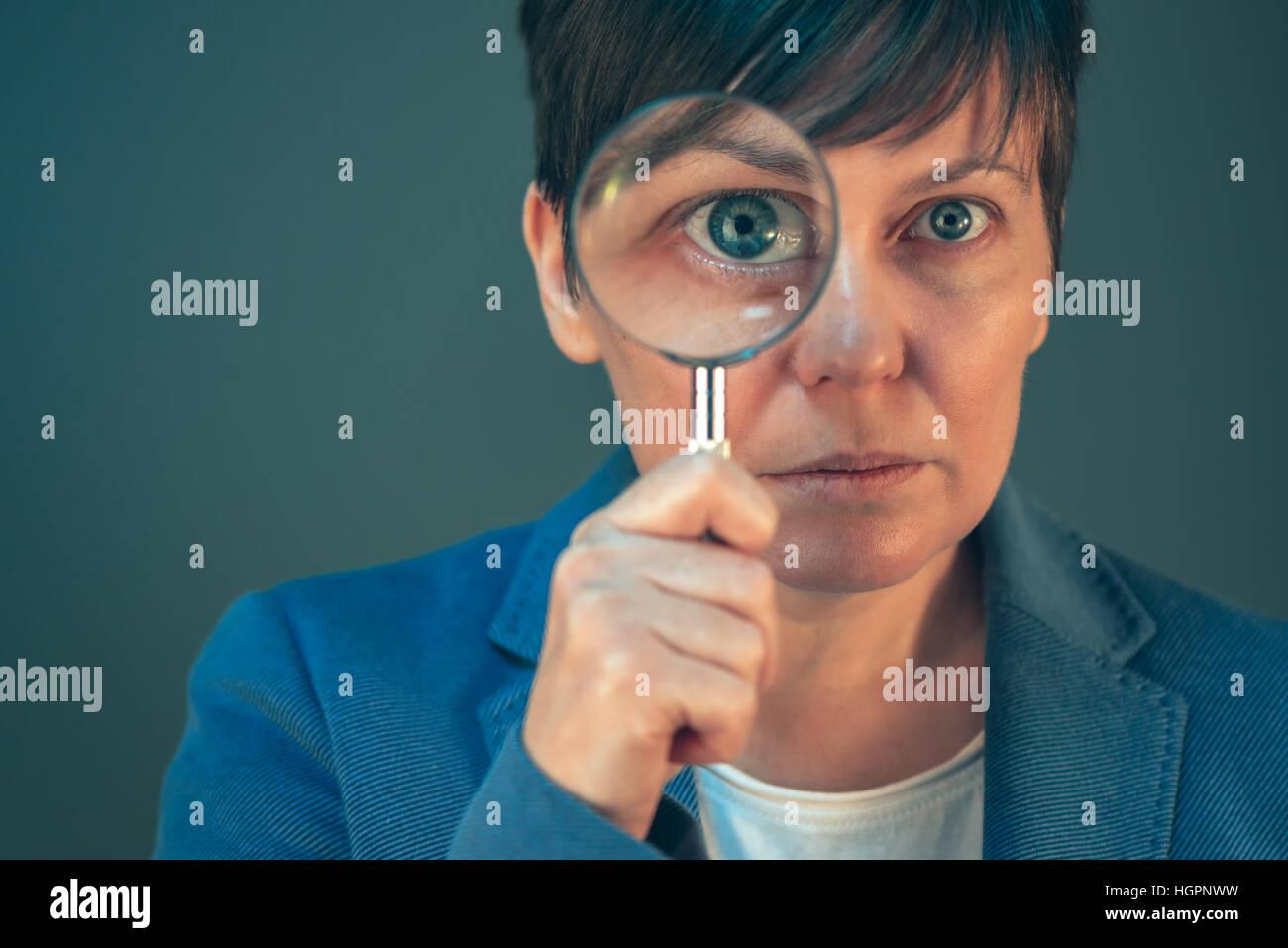 Bella donna d'affari con lente di ingrandimento - cercare, scoprire, esplorare e indagare e analizzare il concetto. Immagini Stock