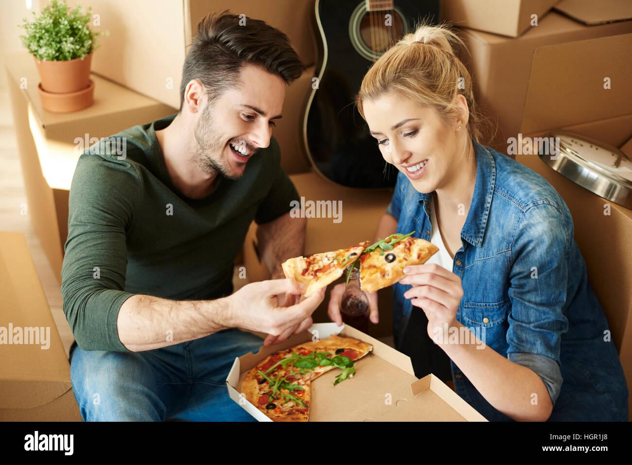 Paio di mangiare pizza accanto a contenitori per il trasloco Immagini Stock
