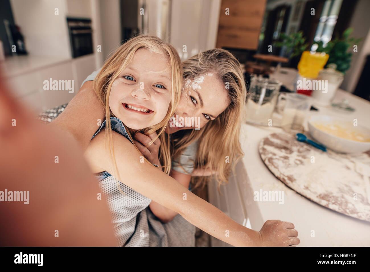 La famiglia felice di prendere una selfie in cucina durante la cottura dei cibi. Madre e figlia tenendo self portrait. Immagini Stock