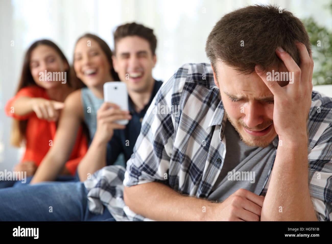 Amici bullismo di un ragazzo triste e scattare foto con lo smartphone per la rete sociale Immagini Stock