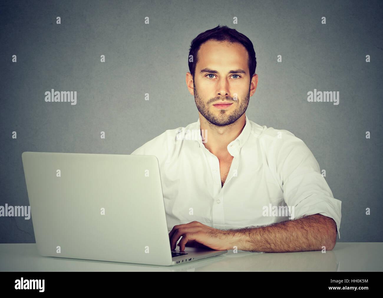 Sorridente giovane uomo d affari usando un computer portatile Immagini Stock
