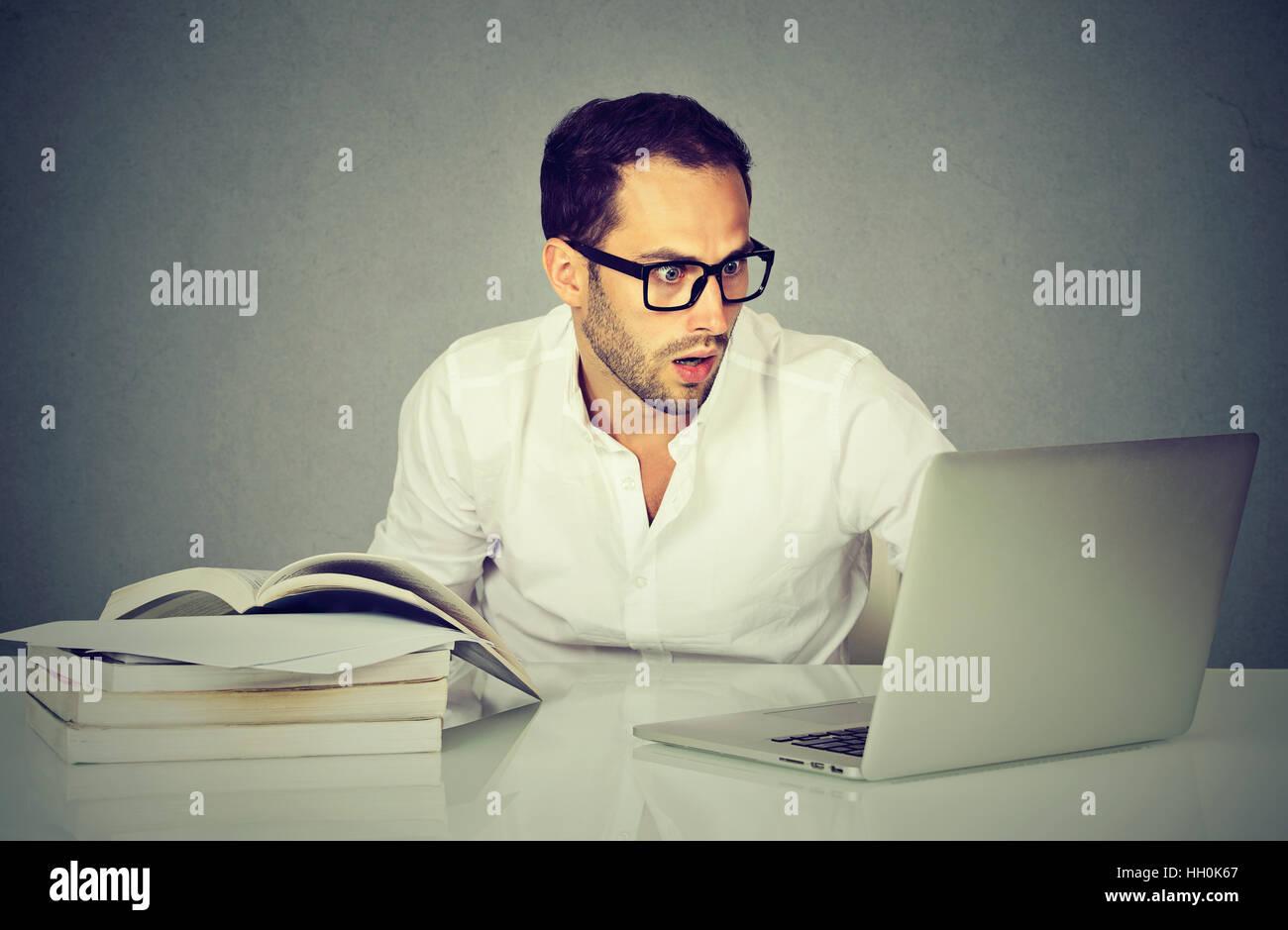 Giovani sorpresi business uomo al lavoro con il computer portatile Immagini Stock