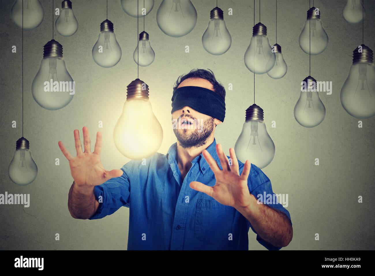 Gli occhi bendati giovane uomo a piedi attraverso lampadine ricerca per la brillante idea Immagini Stock
