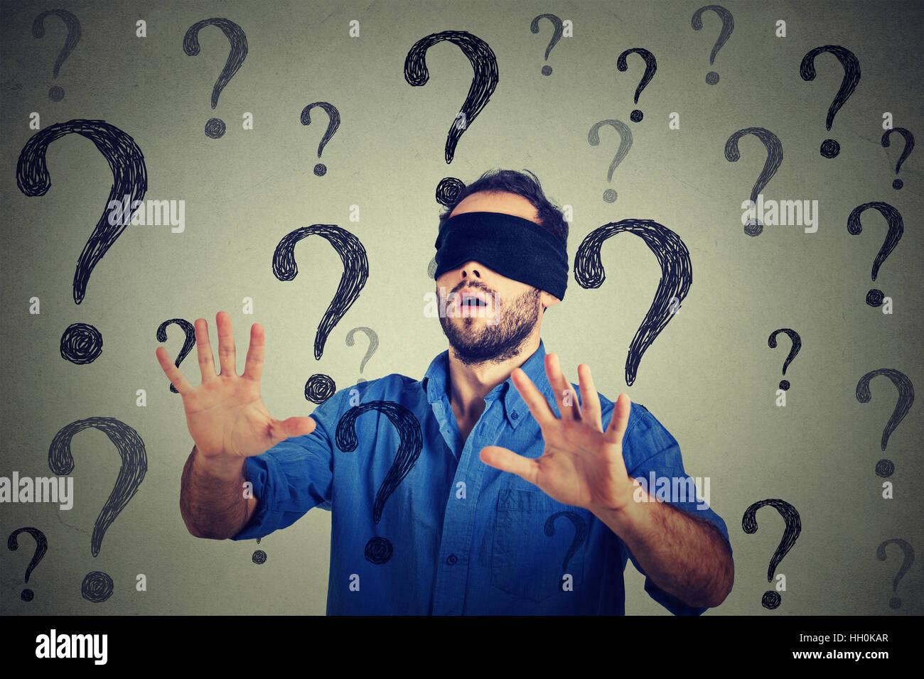 Ritratto uomo d affari con gli occhi bendati stretching braccia fuori a piedi attraverso molte domande isolato sul Immagini Stock