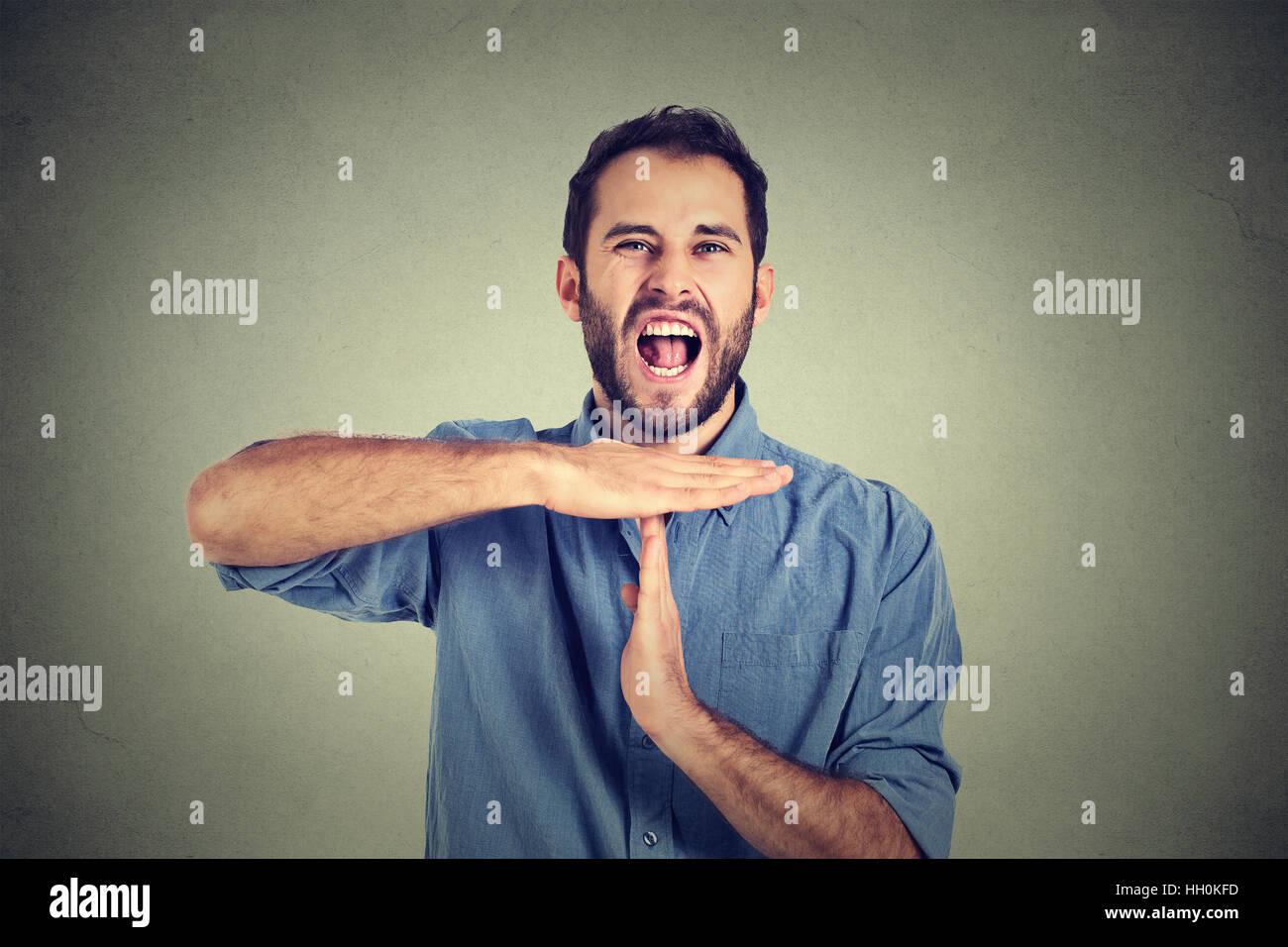 Uomo che mostra il tempo fuori mano gesto, frustrato urlando per arrestare isolato sulla parete dello sfondo. Troppe Immagini Stock