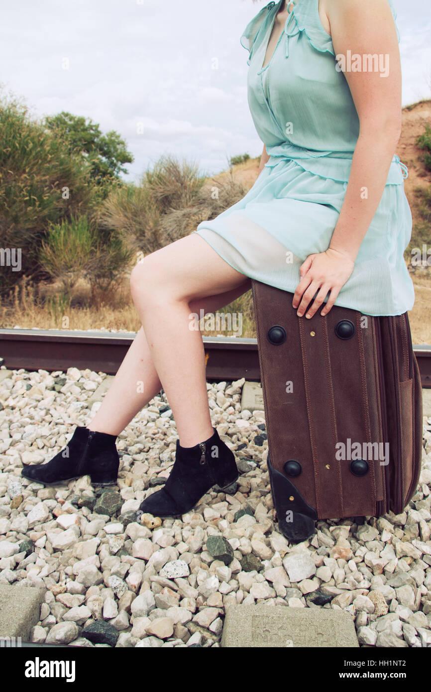 Donna seduta in una valigia vintage Immagini Stock