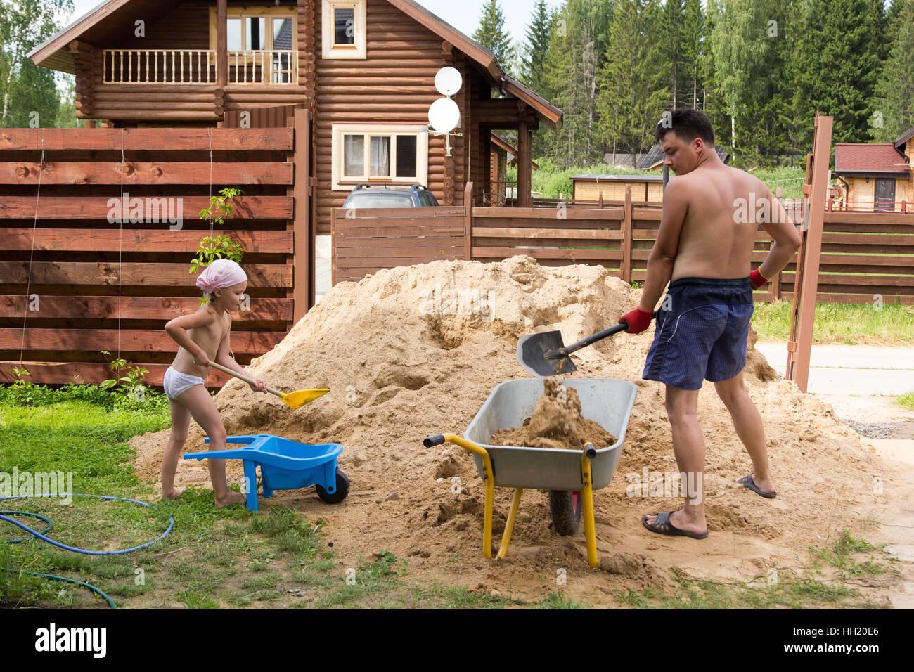 Padre e figlia di carichi sabbia in una carriola Immagini Stock