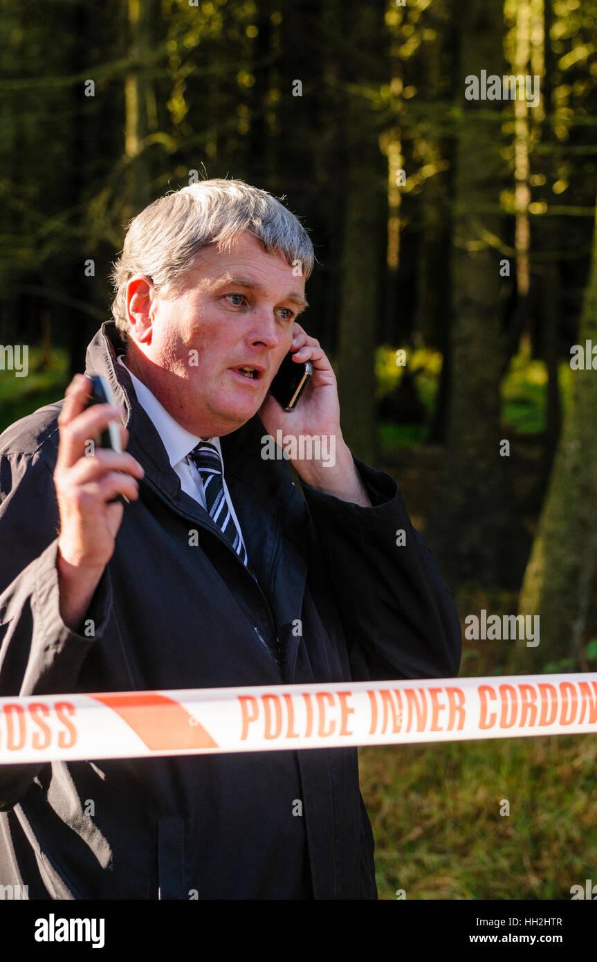 Jim Wells, MLA, (DUP) a parlare su un telefono cellulare mentre in corrispondenza di un cordone di polizia. Immagini Stock