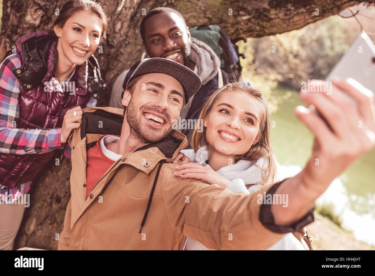 Un gruppo di giovani in piedi vicino al grande albero e tenendo selfie vicino tranquilla foresta fiume Immagini Stock