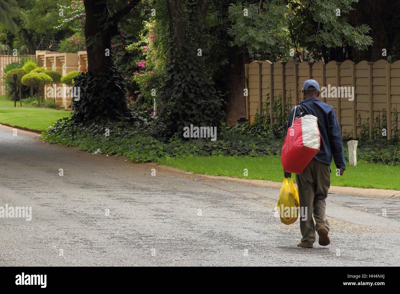 Senzatetto disoccupati uomo Sud Africa cammina giù per una strada pubblica che porta le sue cose immagine con Immagini Stock
