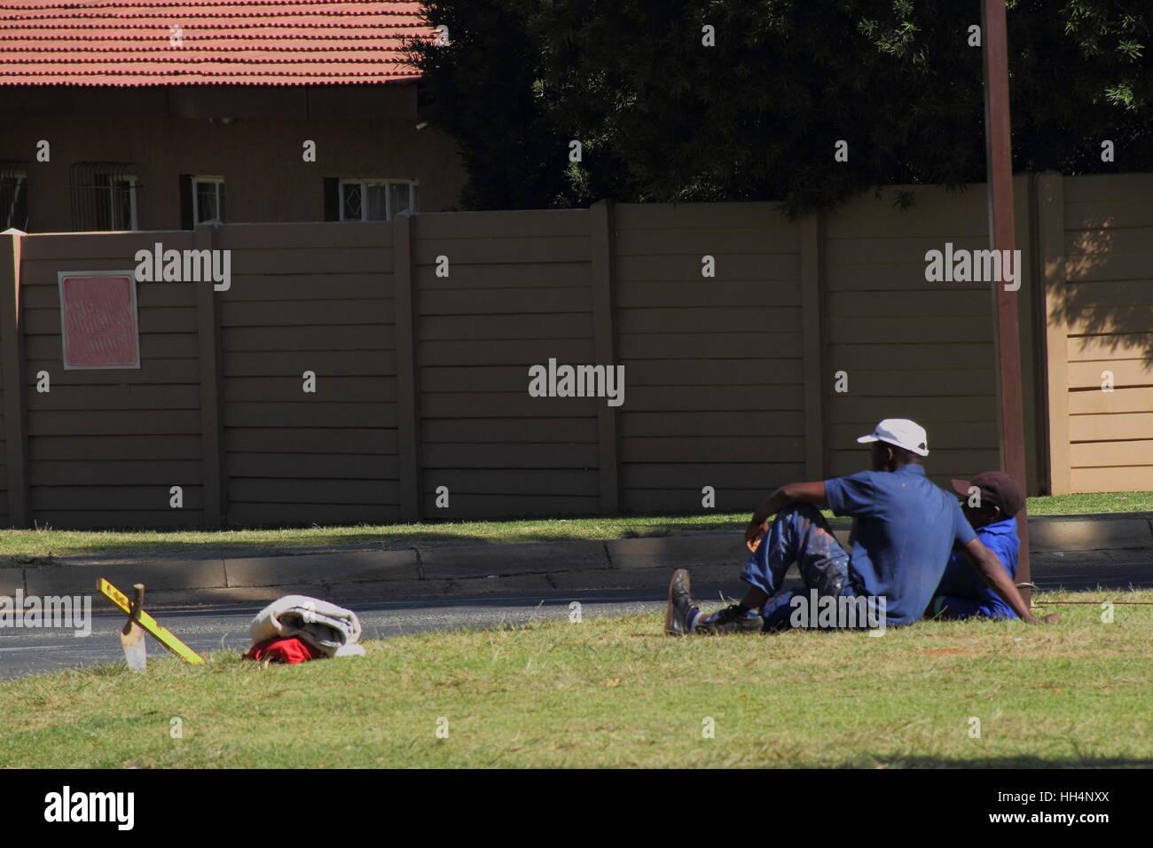 Il tasso di disoccupazione in Sud Africa post-apartheid - disoccupati uomini seduti ad angolo di strada immagine Immagini Stock