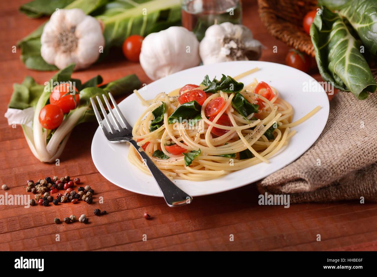 Spaghetti con bietole e pomodoro - il cibo italiano Immagini Stock