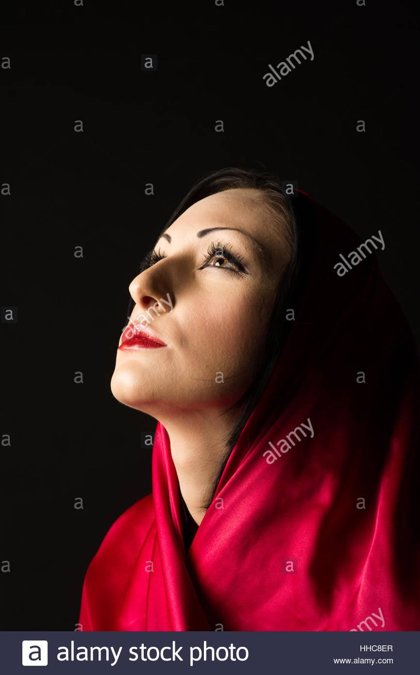 a488ff25fd4f Giovane e bella metà donna orientale in un velo di colore rosso su sfondo  nero.
