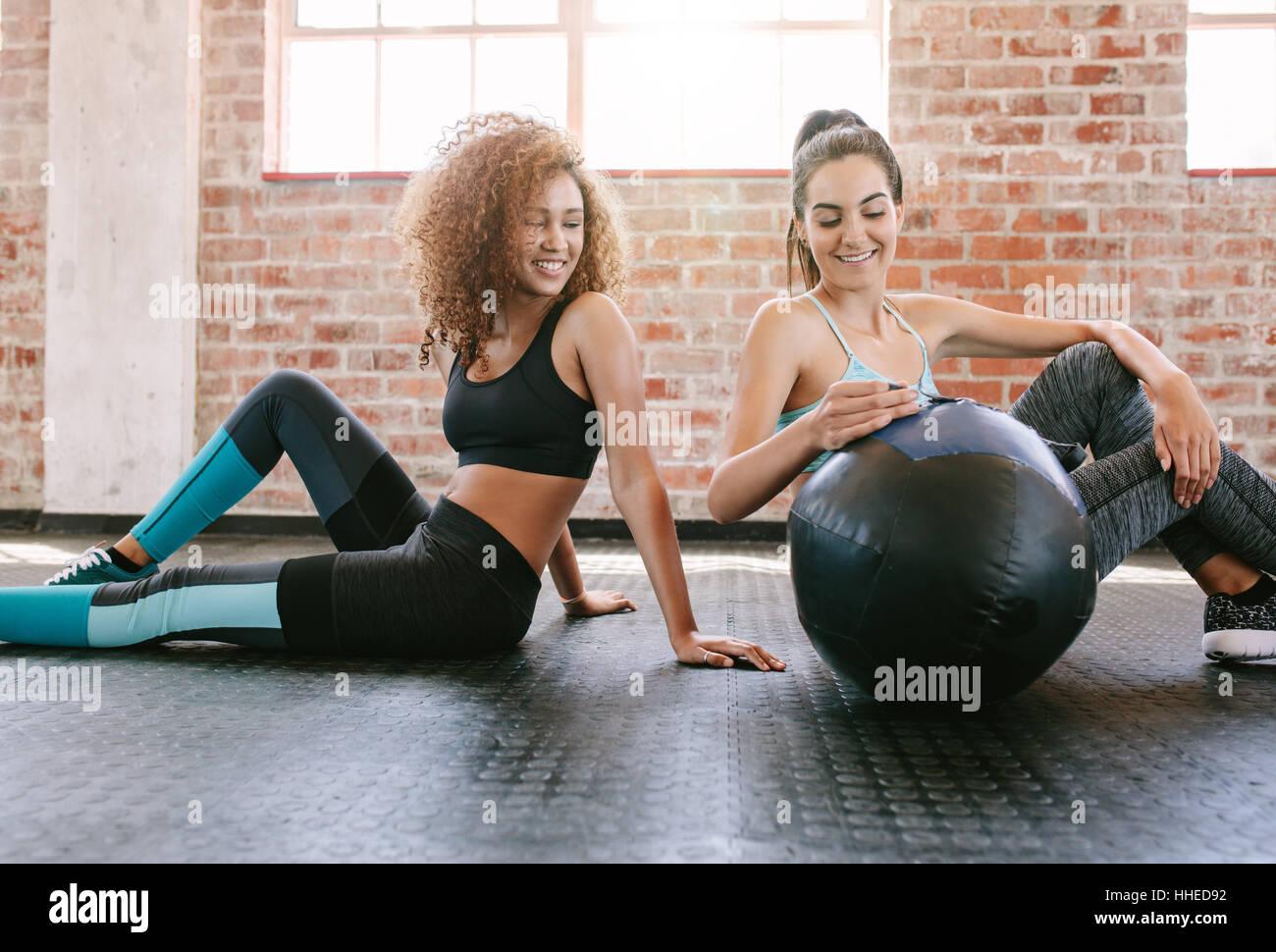 Due giovani amici di sesso femminile seduta sul pavimento Palestra con palla medica. Giovane donna che lavora fuori Immagini Stock