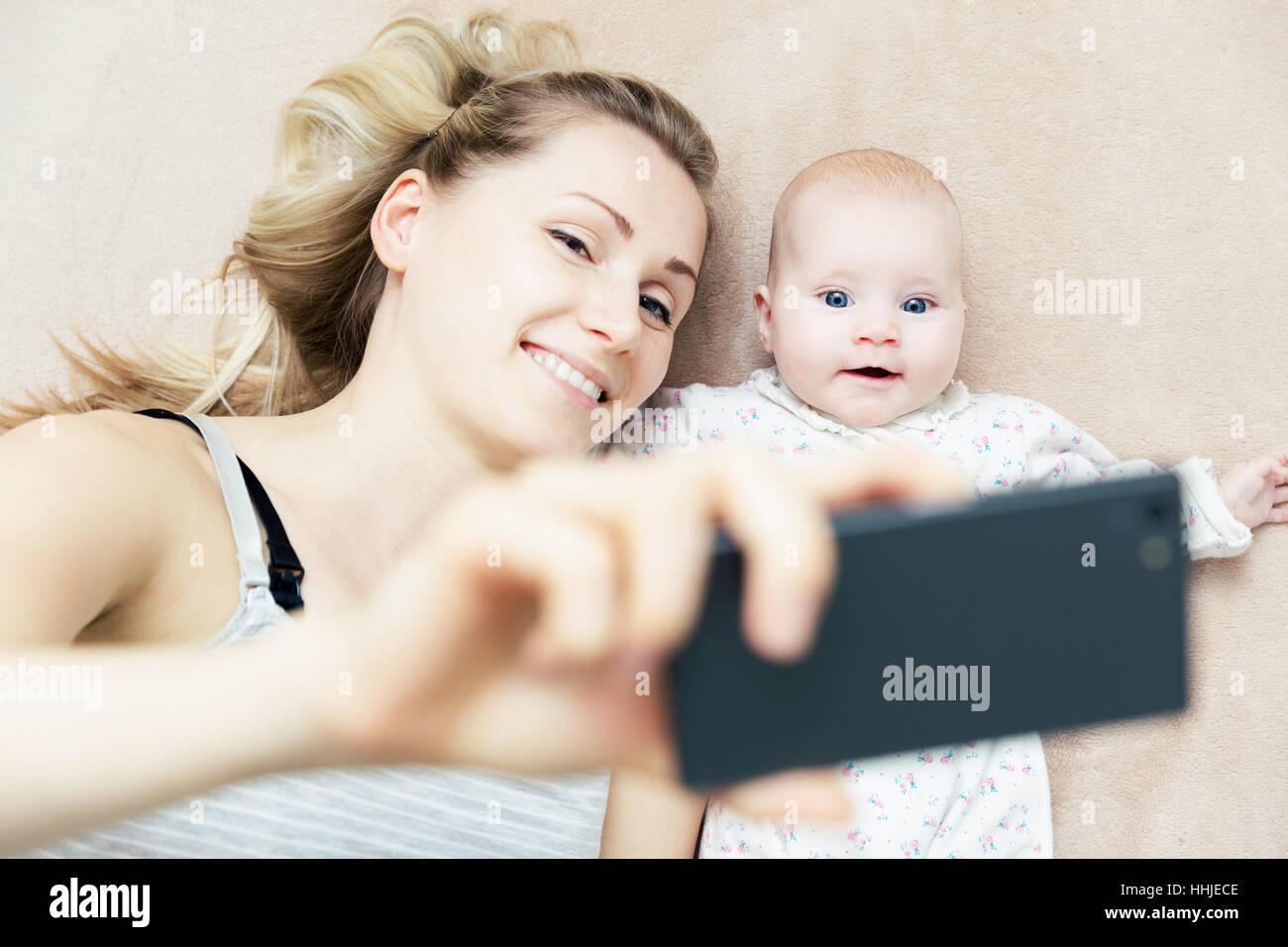 La madre e il piccolo bambino neonato tenendo selfie con telefono a letto Immagini Stock