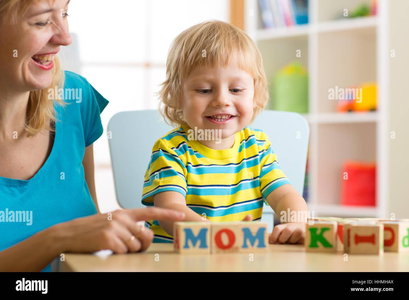 La Madre insegna il figlio bambino per leggere le lettere e parole giocando con cubi Foto Stock