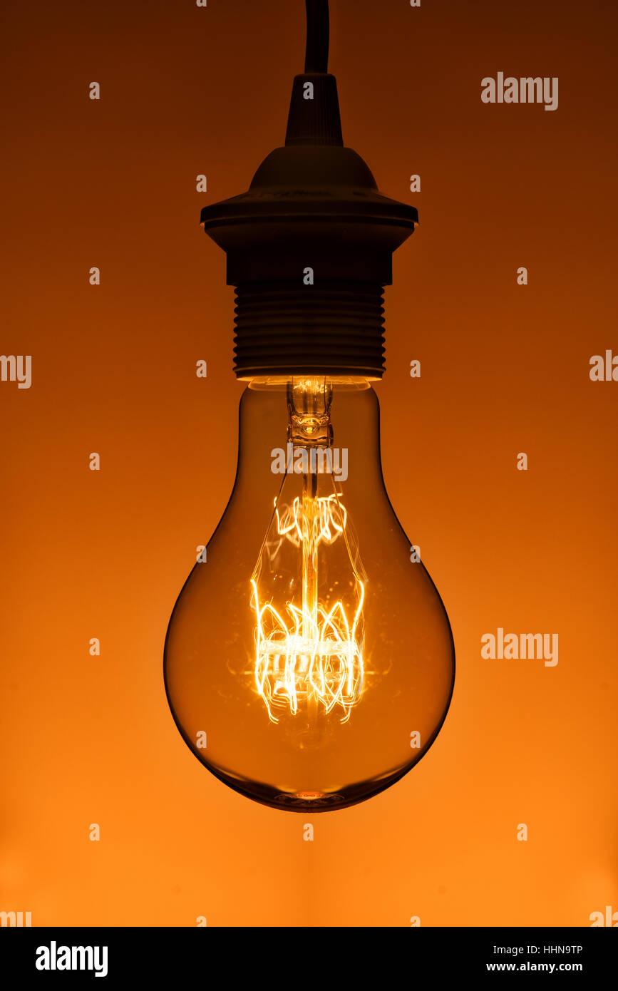 Vintage illuminato lampadina a incandescenza su sfondo arancione Immagini Stock
