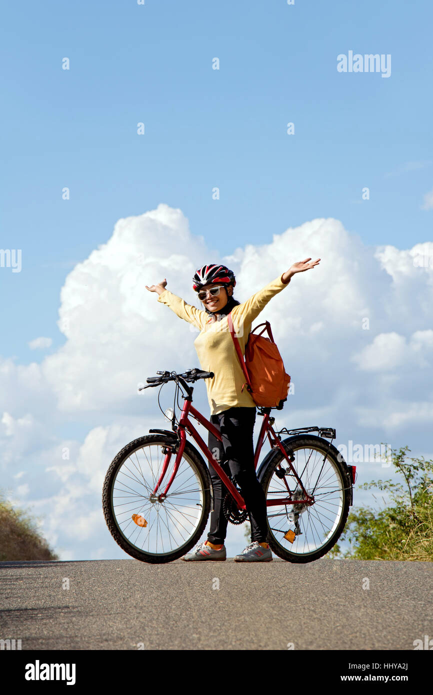 Donna ciclista in piedi con una bicicletta su strada i trend con orizzonte di riferimento e le mani alzate verso Immagini Stock