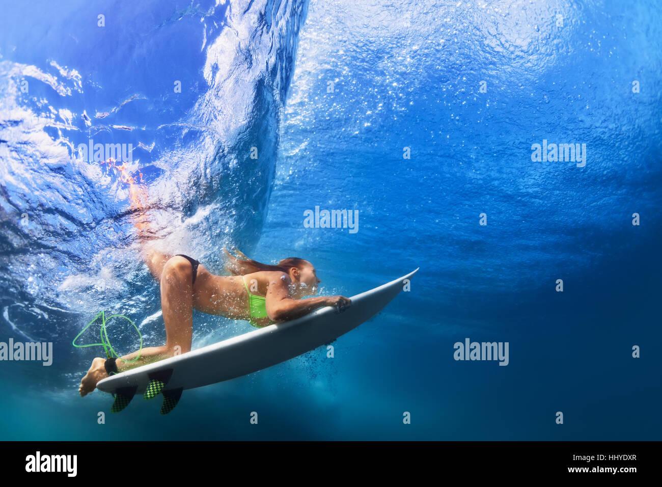 Active Ragazza in Bikini in azione. Surfer donna con tavola da surf tuffarsi underwater in onda. Sport acquatici, Immagini Stock