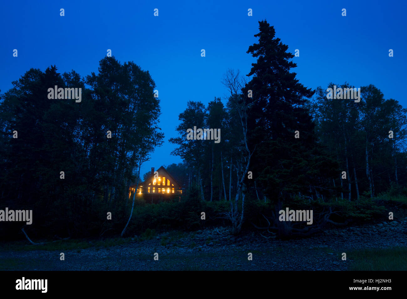 Un log cabin è accesa fino al tramonto lungo un albero coperto riva. Immagini Stock