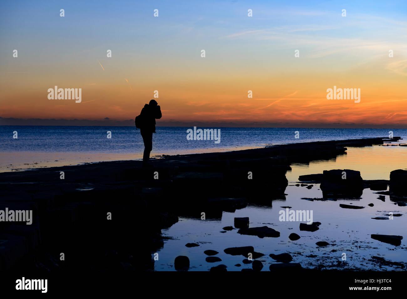 L'uomo stagliano al tramonto sul litorale Immagini Stock