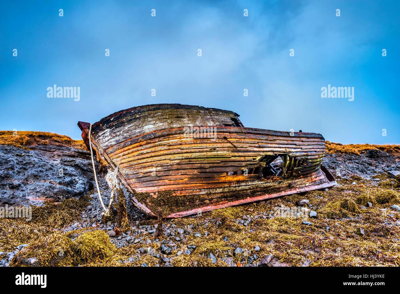 Un vecchio abbandonato nave da pesca dai primi del novecento si appoggia su una spiaggia remota come La vendetta Immagini Stock