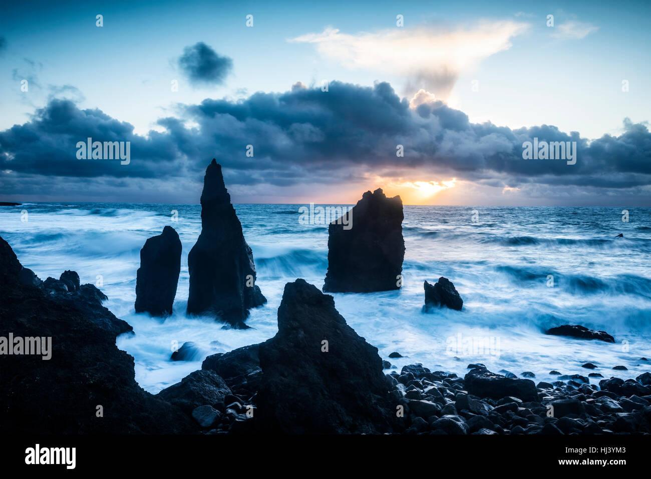 Una spiaggia remota in Islanda mostra sharp scogliere rocciose sporgenti 20 piedi fuori delle acque poco profonde Immagini Stock
