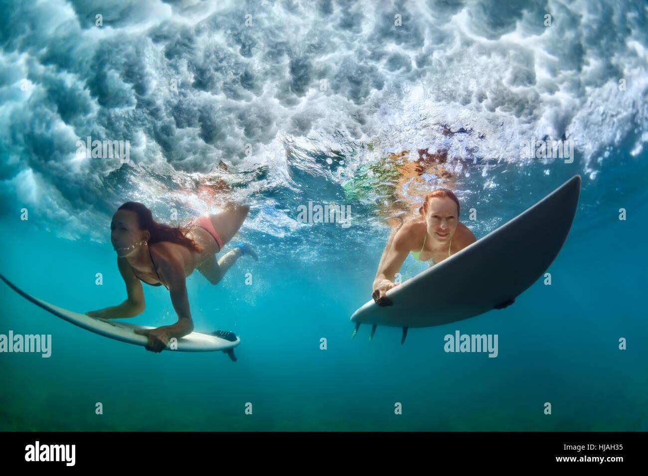 Un gruppo di ragazze attive in azione. Surfer donne con tavola da surf tuffarsi underwater in onda. Sport d'acqua, Immagini Stock