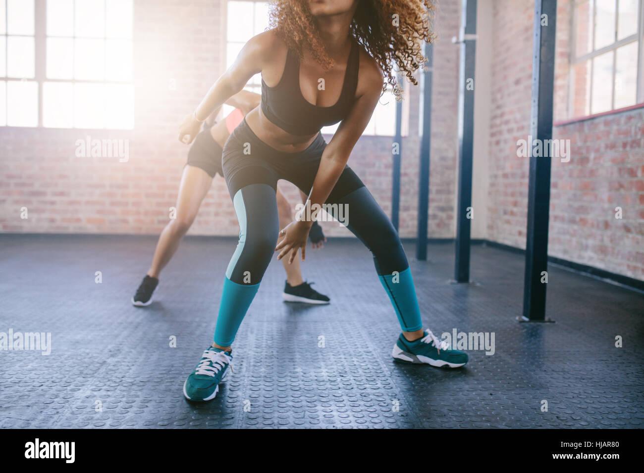 Ritagliato colpo di giovani femmine facendo esecuzione di allenamento in palestra. Focus sulle gambe delle donne. Immagini Stock