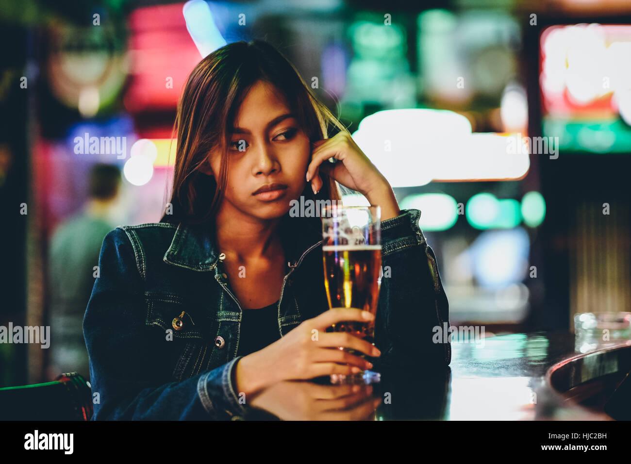 La vita notturna, ragazza per adulti in attesa nel bar a bere bear Immagini Stock