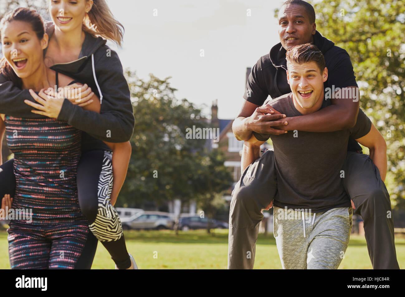 Gli uomini e le donne con formazione di divertimento nel parco, avente piggy back gara Immagini Stock