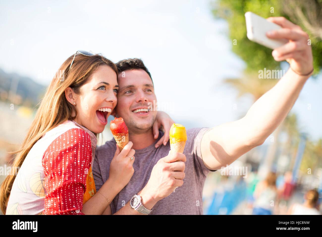 Giovane tenendo selfie mangiare coni gelato, Maiorca, SPAGNA Immagini Stock