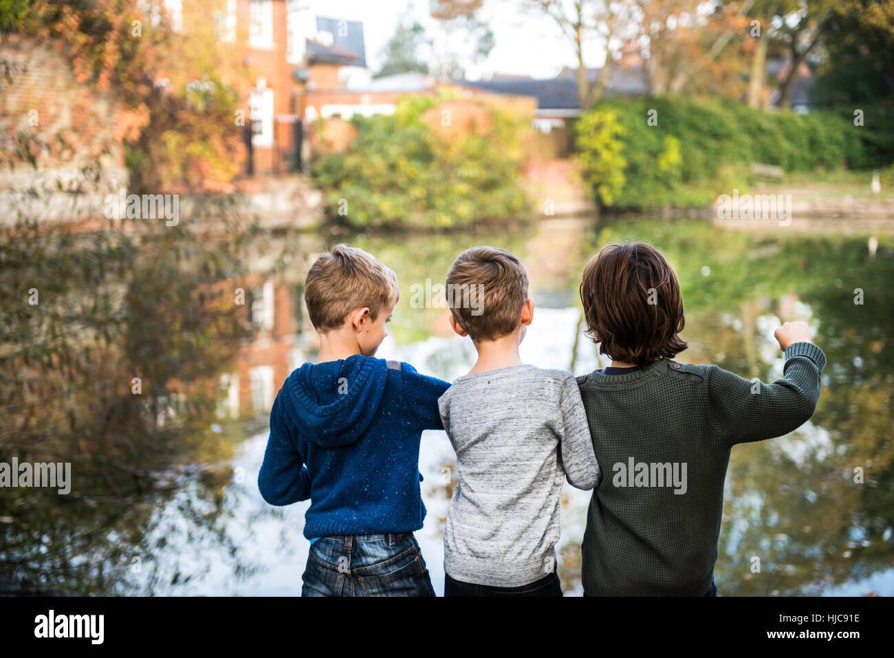 Tre giovani ragazzi, in piedi accanto al lago, vista posteriore Immagini Stock
