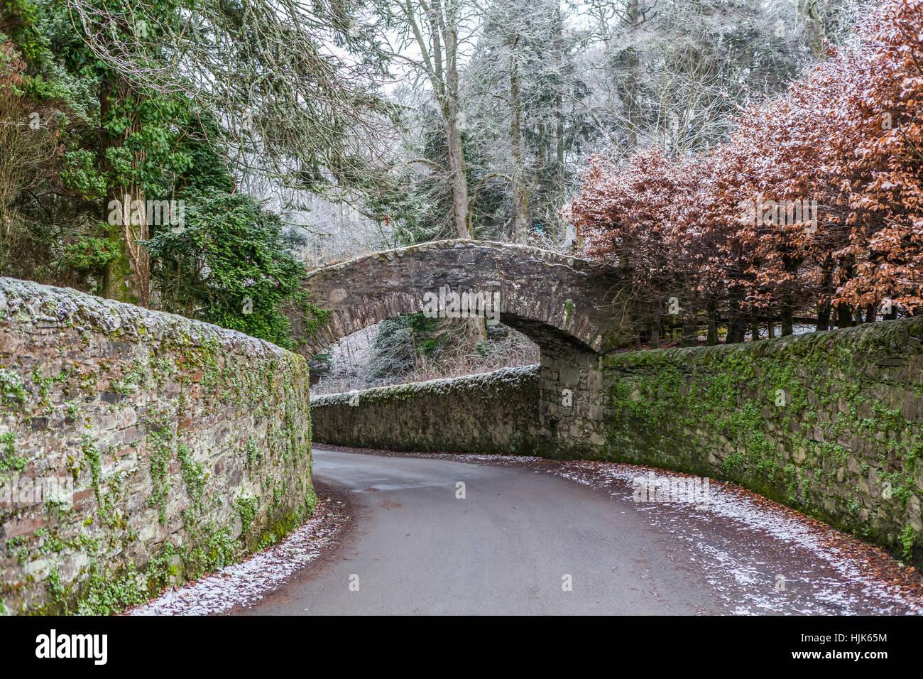 Un vecchio ponte in pietra che attraversa la strada vicino a Glen Tilt, Perthshire, Scotland, Regno Unito Immagini Stock