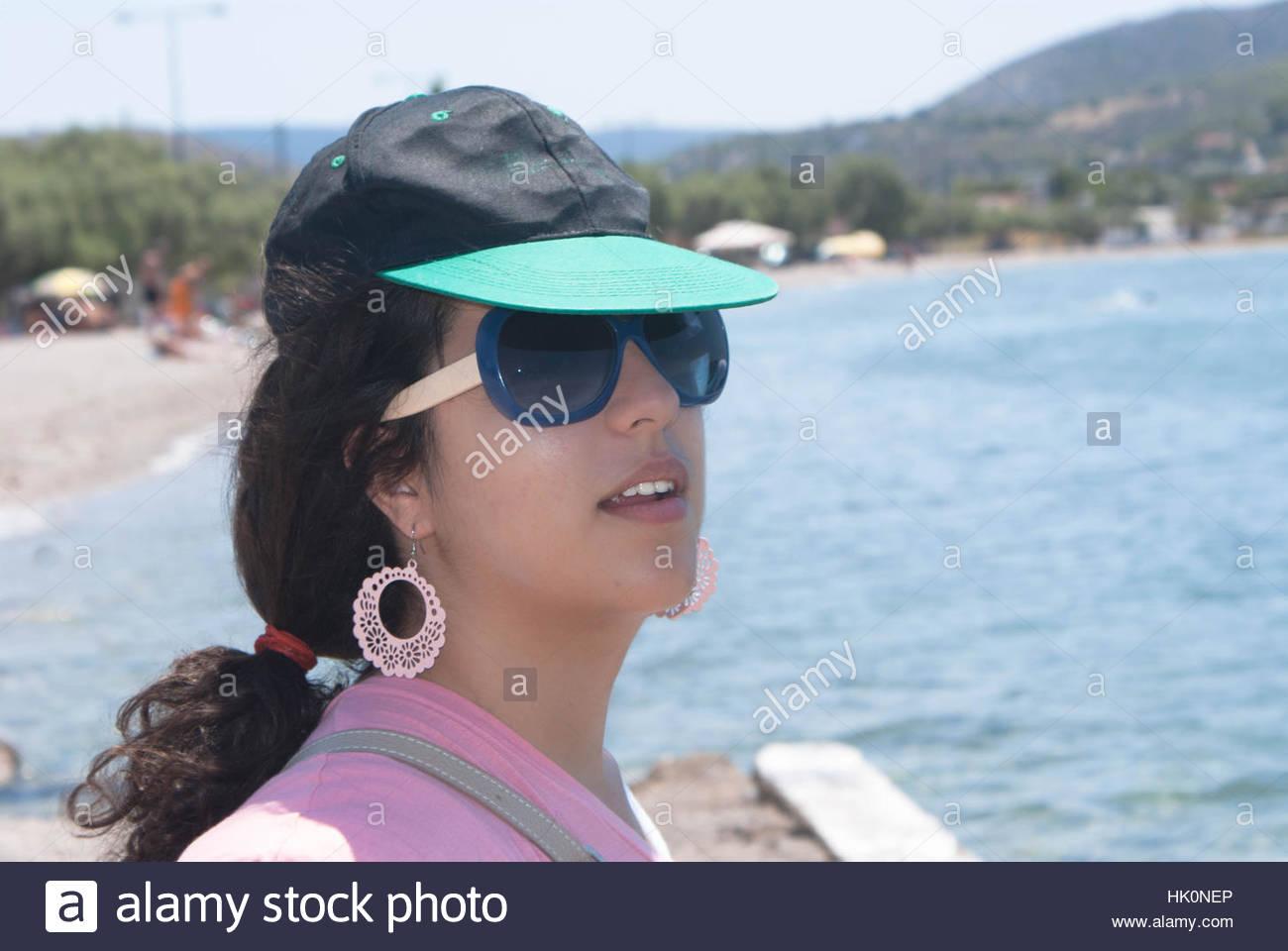Donna che indossa un cappello e occhiali da sole in spiaggia Foto ... 4f4cd7a5fda3