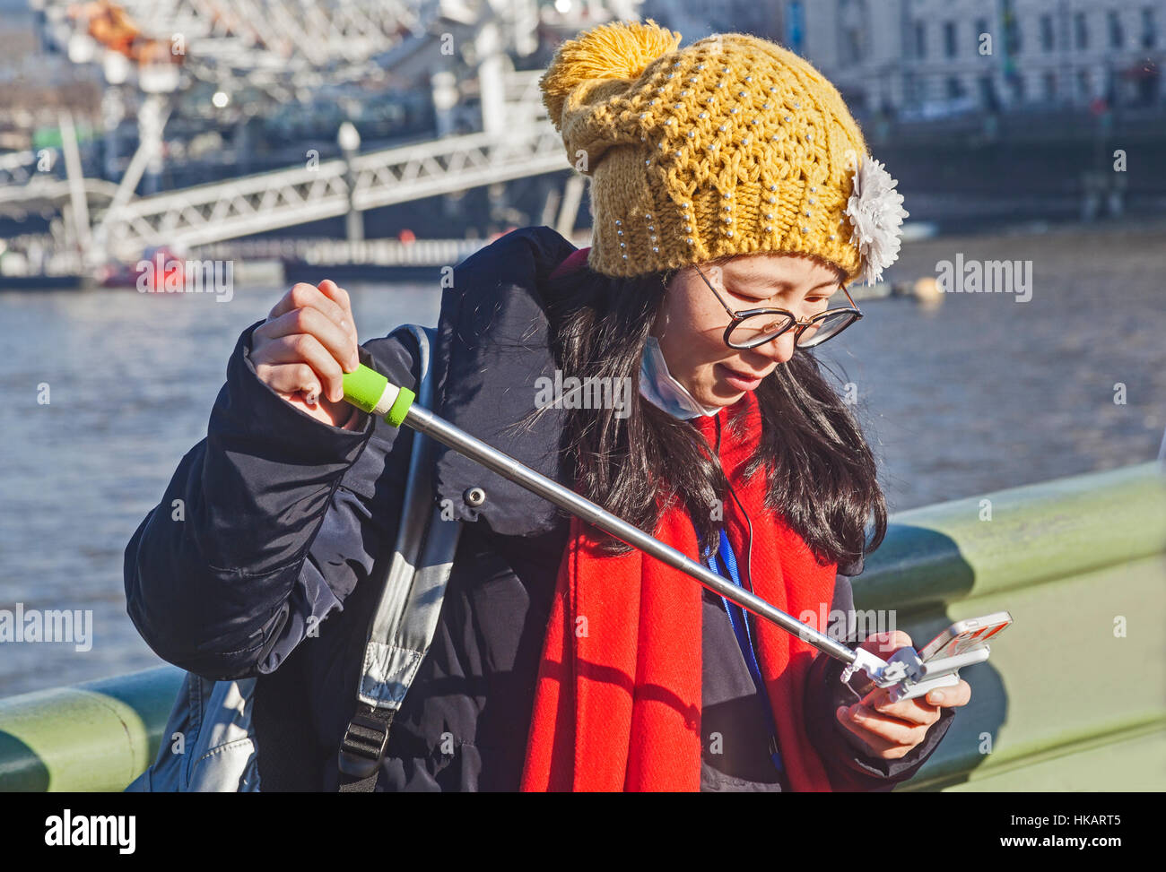 London, Westminster un turista giapponese controlla la sua fotocamera con annesso selfie-stick sul Westminster Bridge Immagini Stock