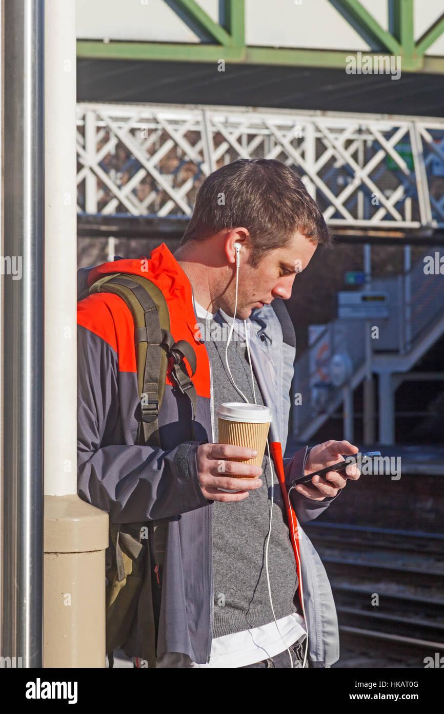 """Un """" commuter """" controllo del suo Io telefono a Brockley stazione ferroviaria a Lewisham Immagini Stock"""