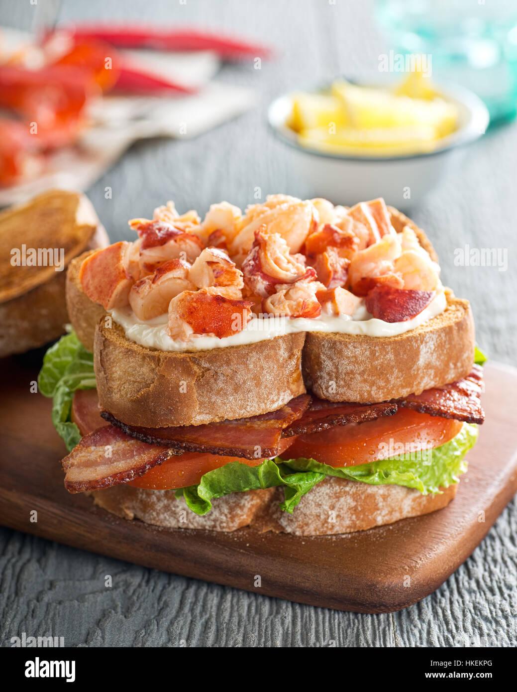 Una deliziosa aragosta club sandwich con bacon, lattuga, pomodoro e maionese sul pane tostato. Foto Stock