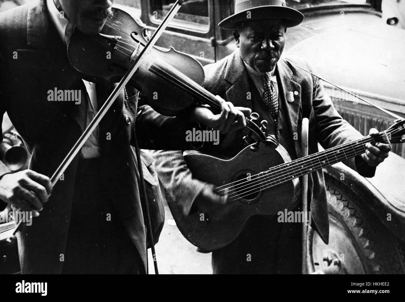 Fotografia in bianco e nero di due uomini afro-americano, musicisti di strada, uno a suonare il violino e l'altra Immagini Stock