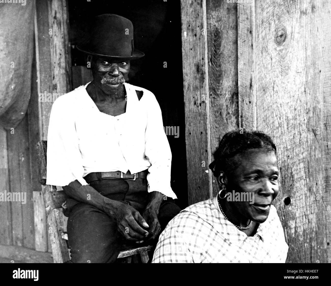 Fotografia in bianco e nero di due coppia afro-americano di mezzadri, una donna seduta in primo piano un uomo seduto Immagini Stock