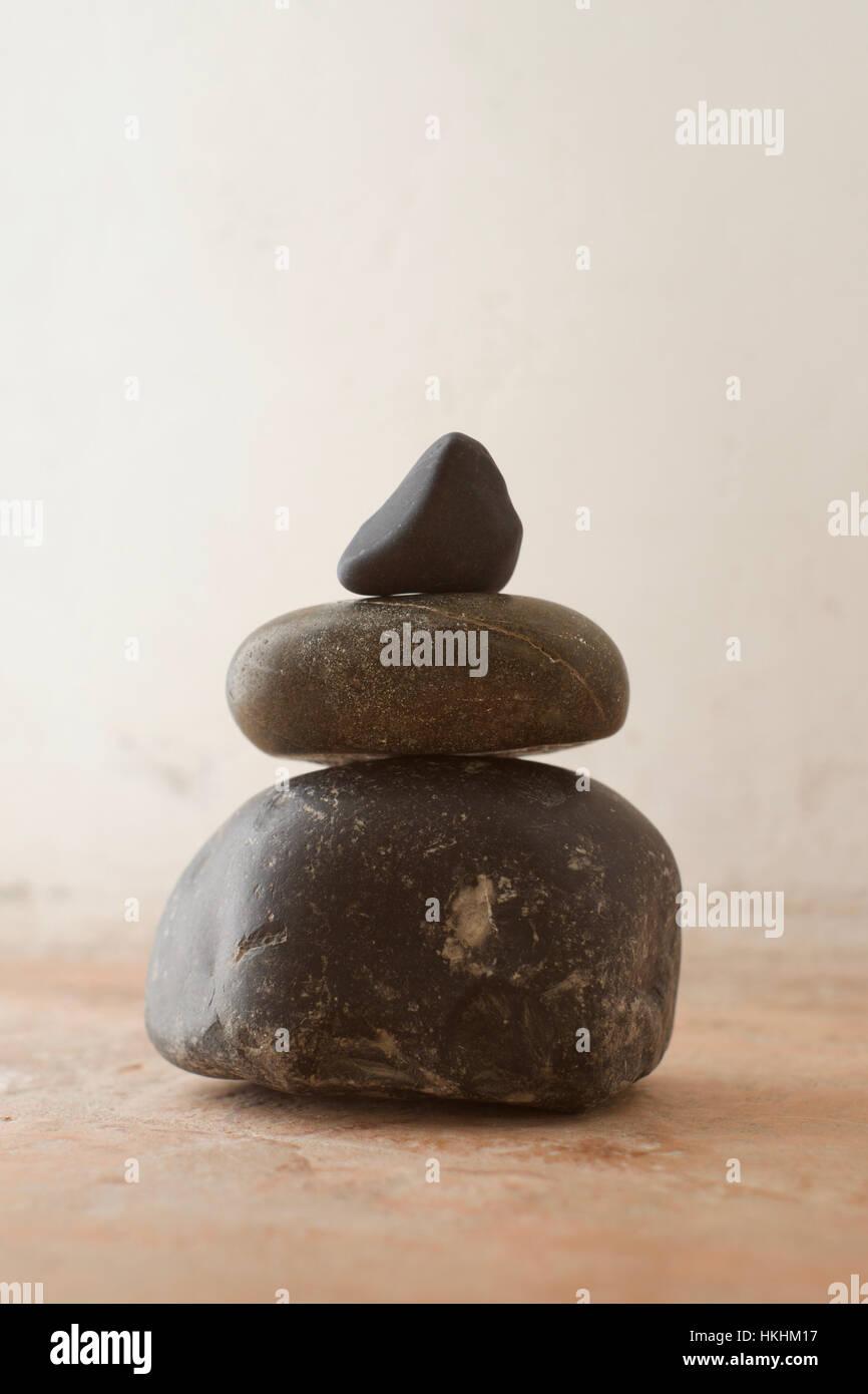 Una pila di ciottoli con toni di nero contro un sfondo rustico Immagini Stock