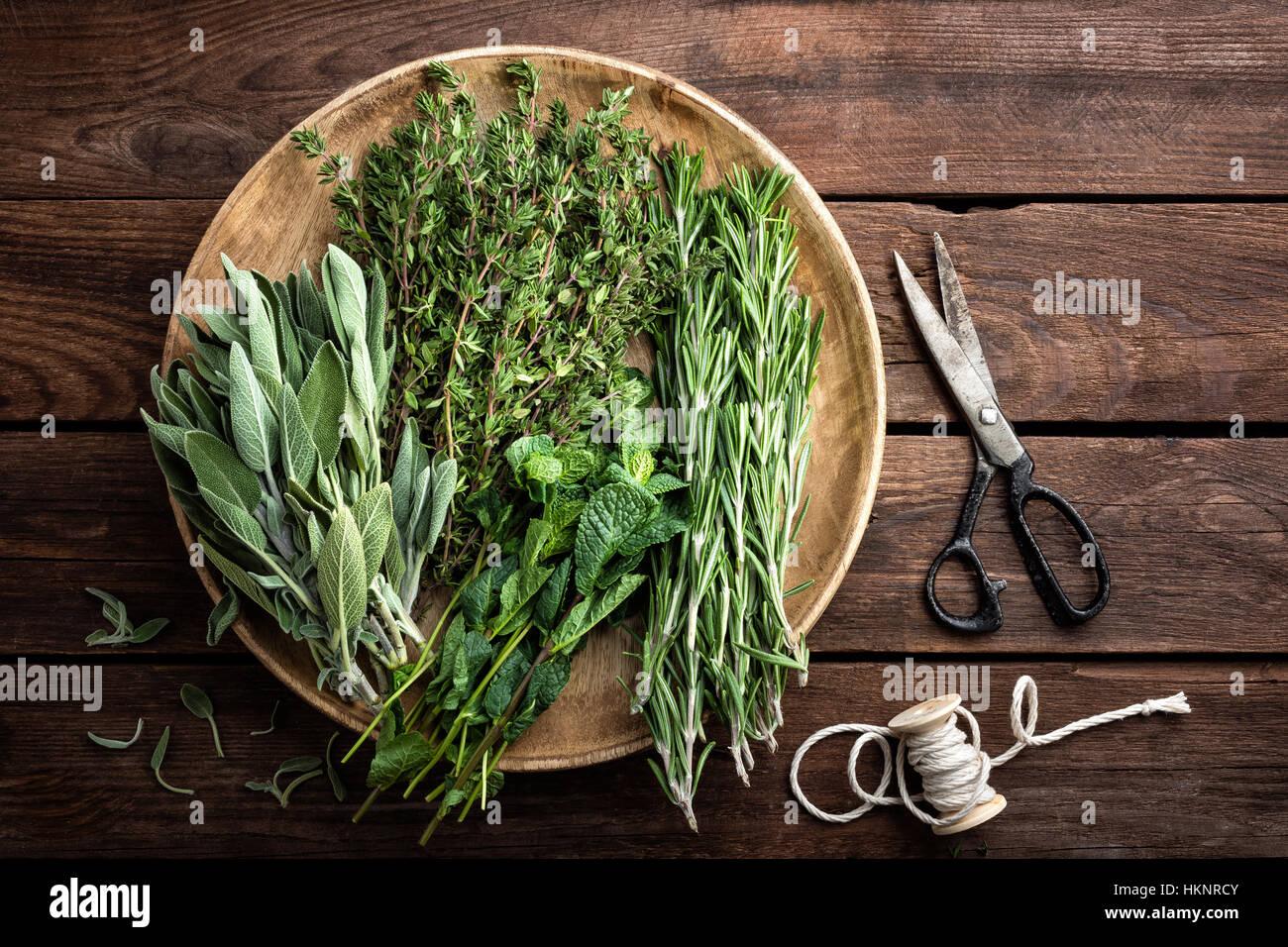 Varie erbe fresche, rosmarino, timo, menta e salvia su sfondo di legno Immagini Stock