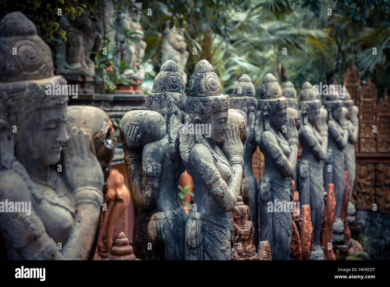 Tradizionali asiatici sculture di divinità del Buddismo in stile vintage nel giardino tropicale che illustra Immagini Stock
