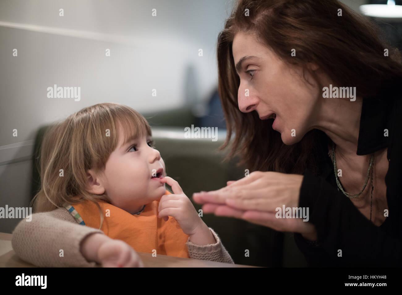 Brunette donna l'espressione del viso e gesti con le mani che raccontano una storia o un racconto, al bambino Immagini Stock