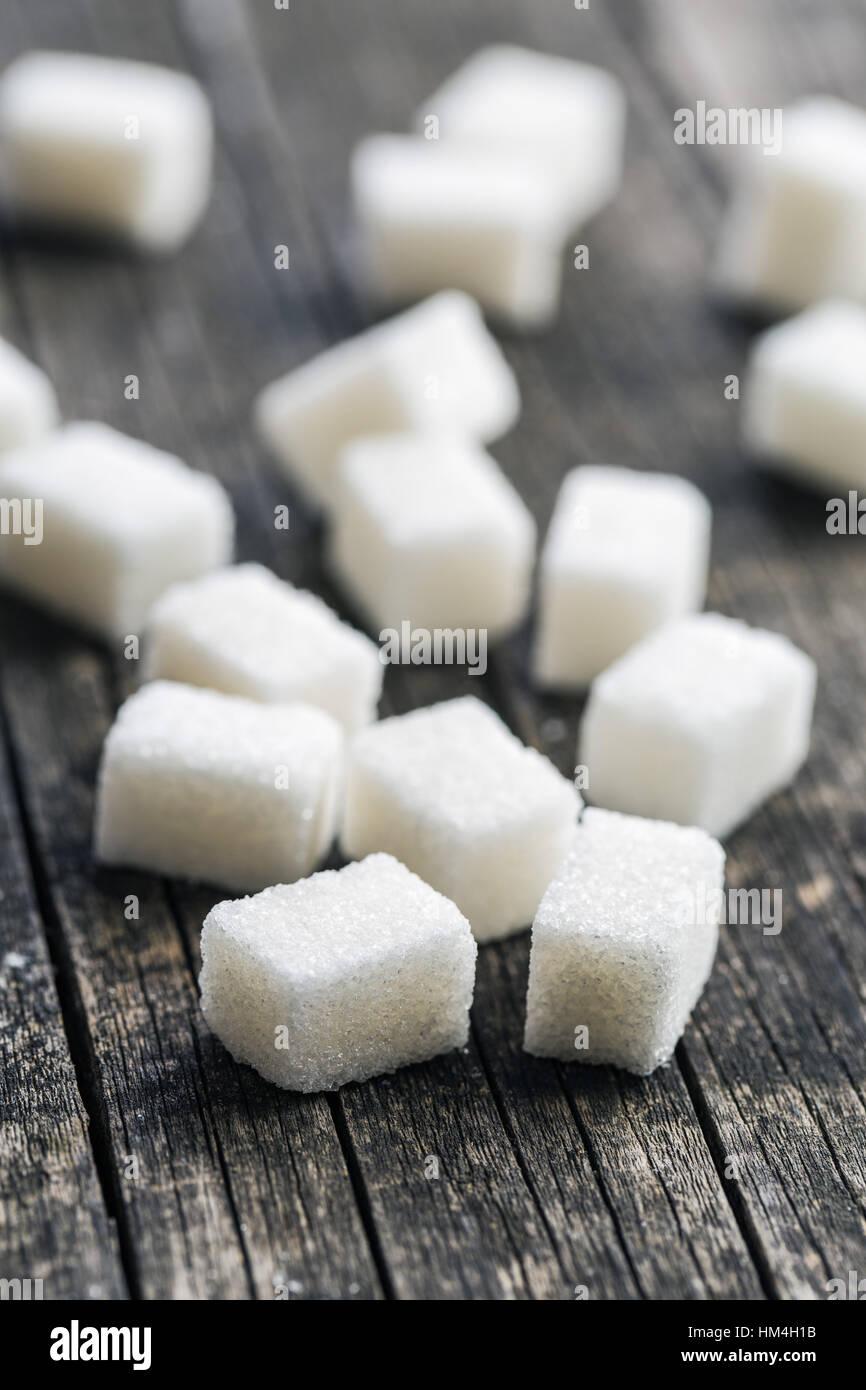 Zucchero bianco i cubi su vecchio tavolo in legno. Immagini Stock