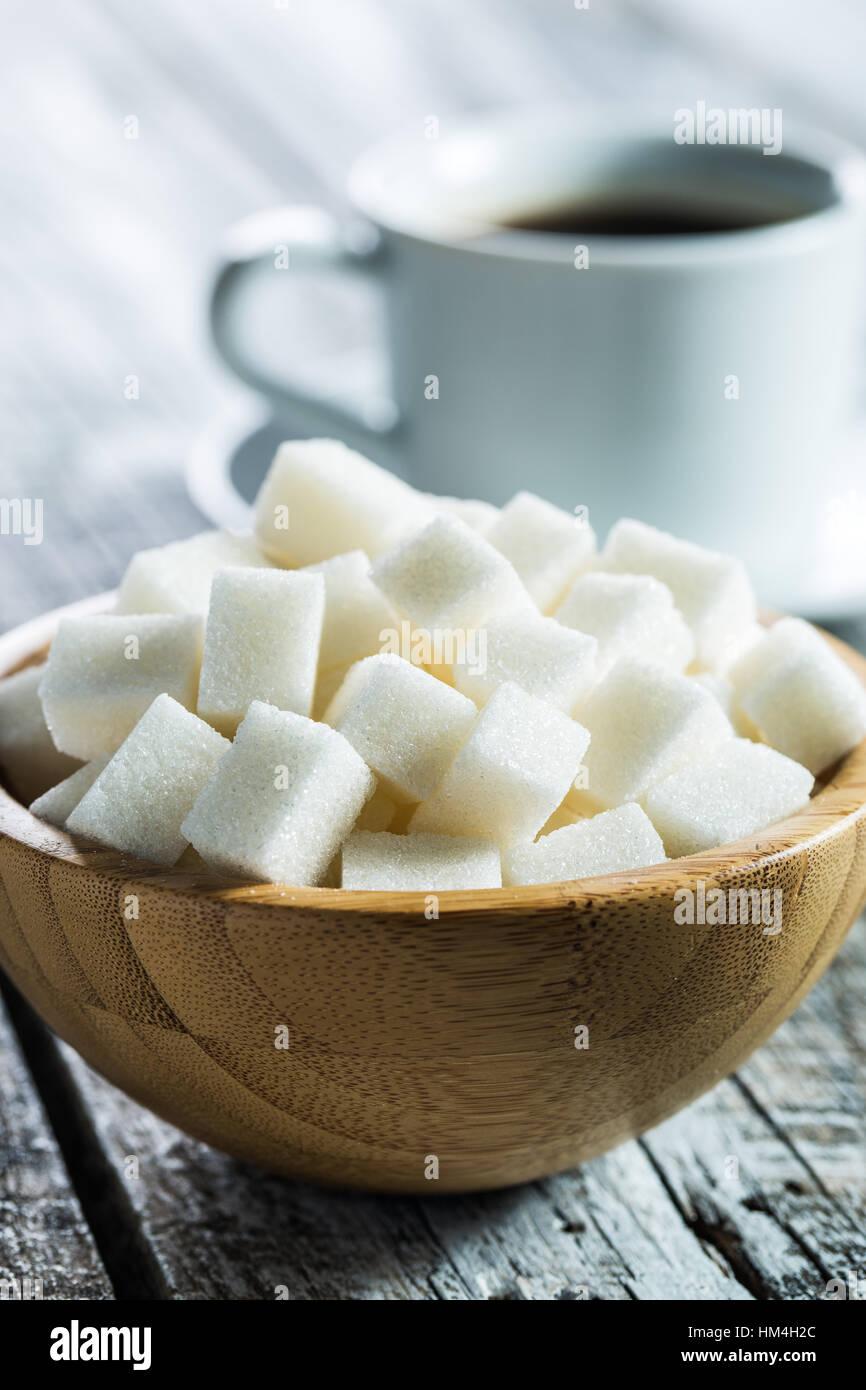 Zucchero bianco cubi nella ciotola di legno. Immagini Stock