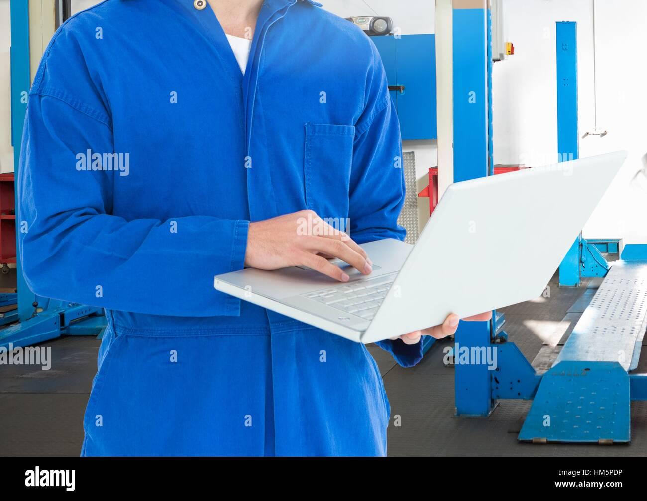 La sezione centrale del meccanico utilizzando laptop Immagini Stock
