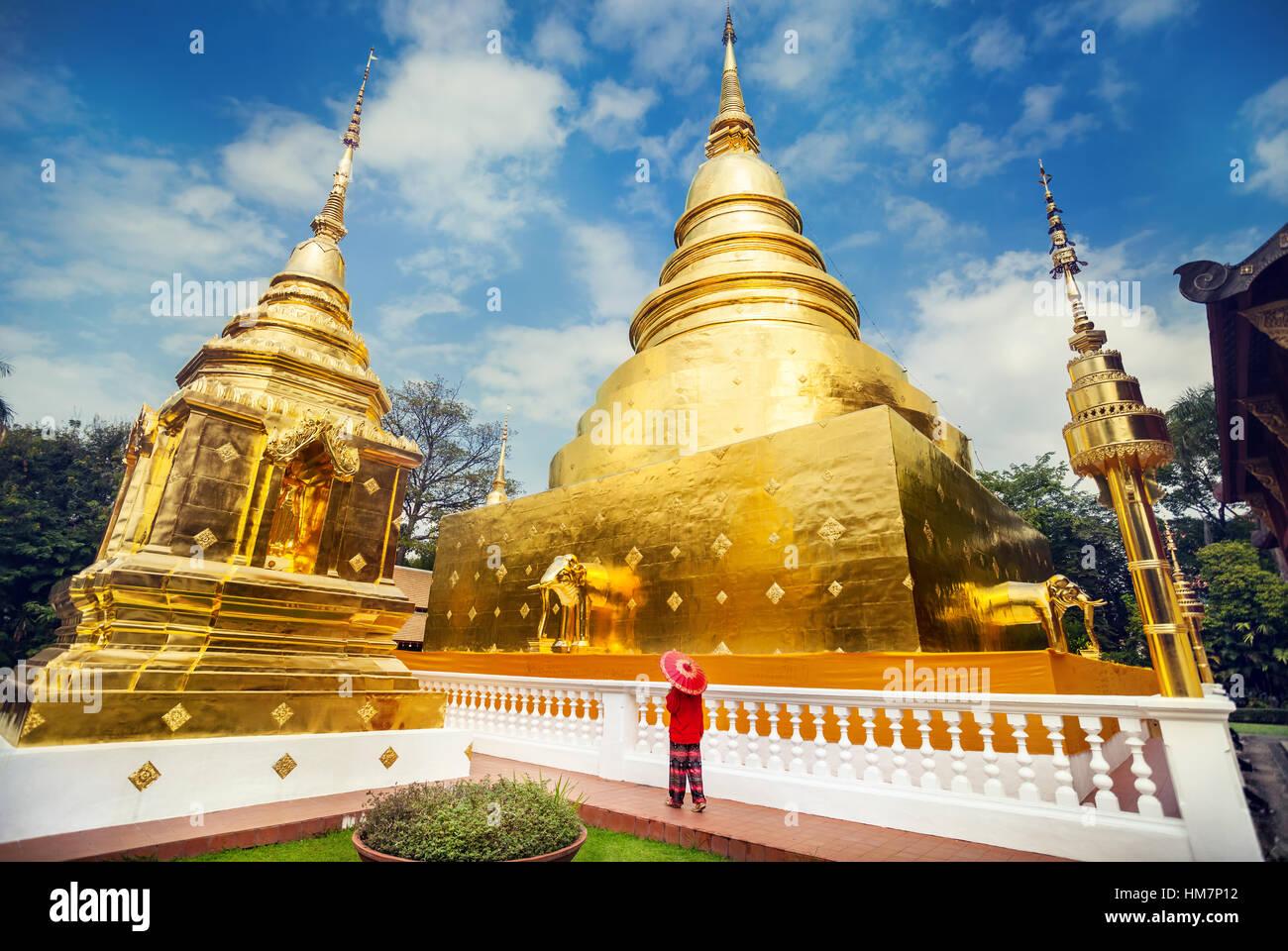 Donna con turistico rosso tailandese tradizionale ombrellone vicino a Golden Stupa al tempio di Wat Phra Singh in Foto Stock