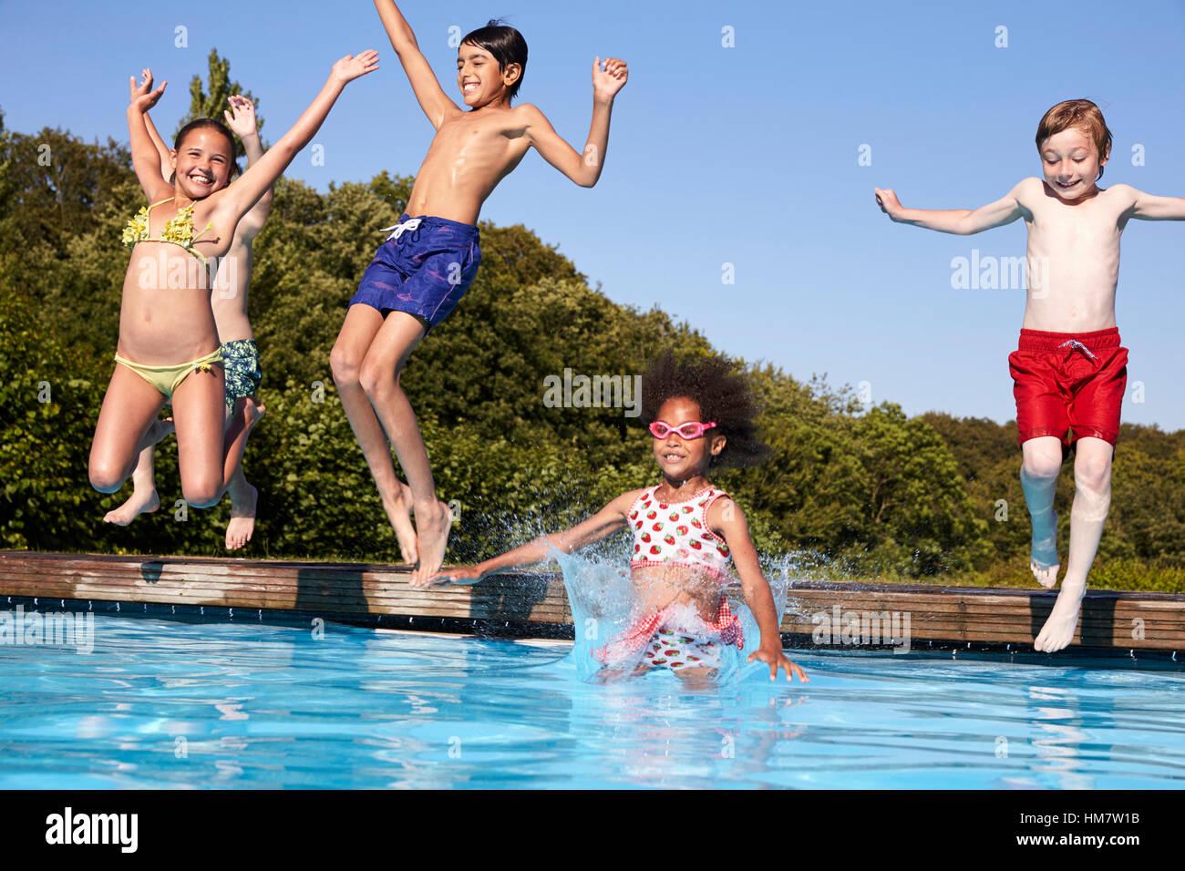 Gruppo di bambini un salto nella piscina esterna Foto Stock